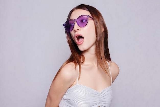 Ritratto di ragazza di bellezza in occhiali sfondo bianco. ritratto ravvicinato di una giovane bella ragazza allegra con i capelli lunghi scuri che sorride con i denti, guardando nella telecamera la ragazza è sorpresa