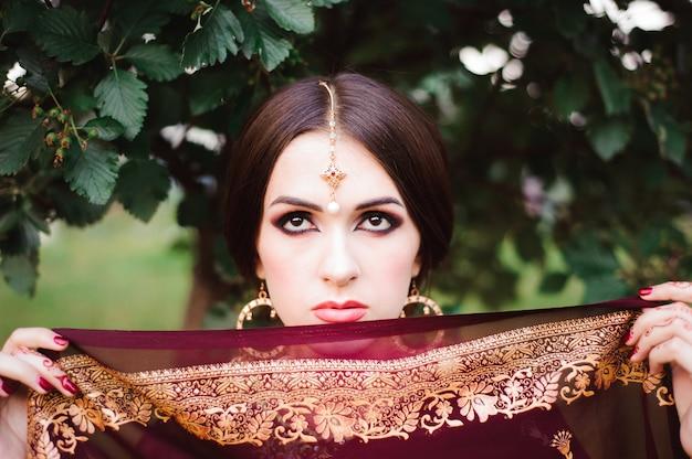 Ritratto di bellezza modella indiana con trucco luminoso che nasconde il viso dietro il velo