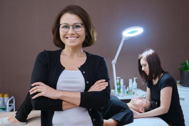 Ritratto di donna proprietaria di un salone di bellezza, in posa femminile sorridente fiducioso maturo, procedura di massaggio di fondo sul tavolo