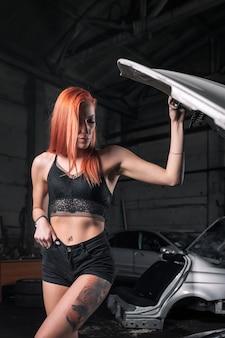 Ritratto di una donna di bellezza in jeans corti e top su uno sfondo di officina.