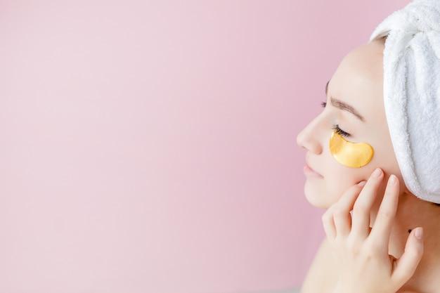 Ritratto della donna di bellezza con le toppe dell'occhio su fondo rosa. fronte di bellezza della donna con la maschera sotto gli occhi.