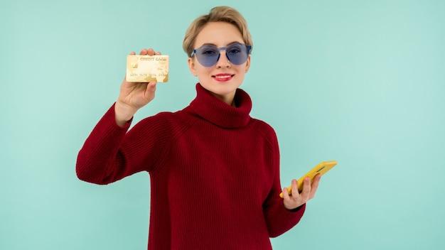 Ritratto di giovane ragazza di bellezza in occhiali da sole che mostra la carta di credito in plastica mentre si tiene il telefono cellulare isolato su sfondo blu