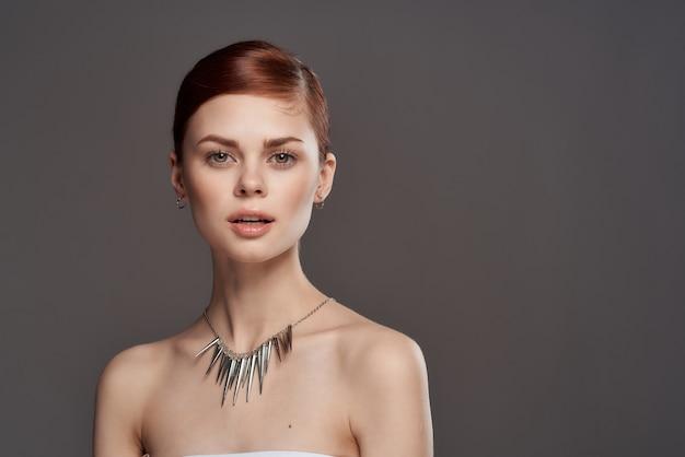 Ritratto di una giovane donna di bellezza, pelle pulita, pubblicità di gioielli, orecchini, anelli, catene,