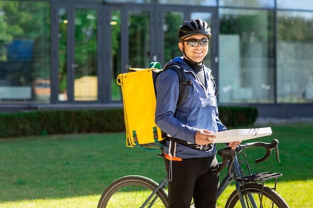 Ritratto del corriere della bicicletta con la borsa e la bici gialle. uomo in casco e vetri che tengono il contenitore di pizza