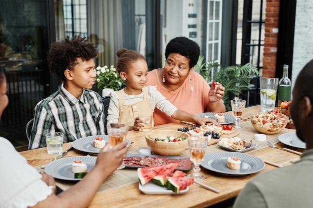 Ritratto di grande famiglia afroamericana che si gode la cena insieme all'aperto e sorride felicemente