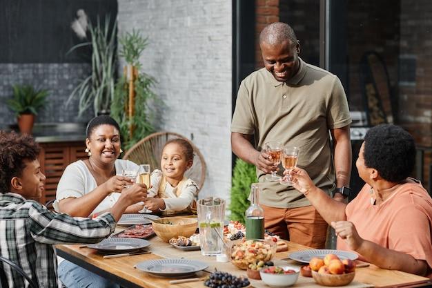 Ritratto di grande e felice famiglia afroamericana che si gode la cena insieme sulla terrazza all'a...