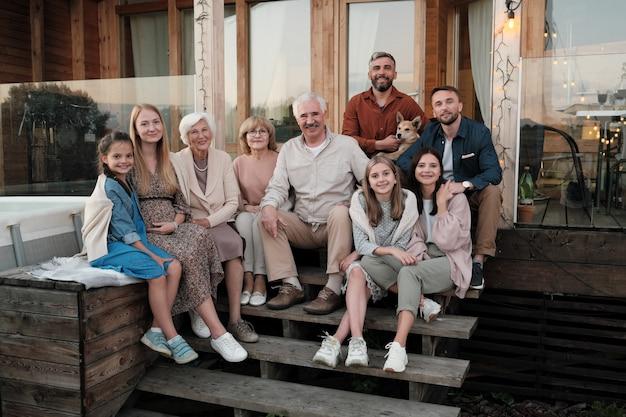 Ritratto di grande famiglia felice seduta sotto il portico e sorridente si sono riuniti nella loro grande casa di campagna