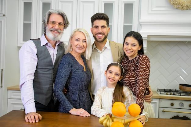 Ritratto di grande felice multigenerazionale insieme in posa per la macchina fotografica in una cucina elegante a casa