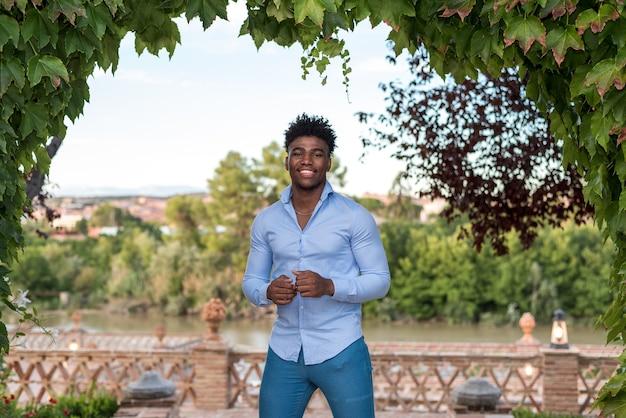 Il ritratto di un ragazzo afroamericano nero si è vestito in sorridere dei jeans e della camicia. alberi e fiume in background.