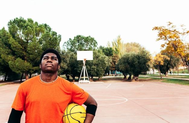 Ritratto di un ragazzo afro nero con uno sguardo di sfida e un pallone da basket in mano. pronto per giocare.