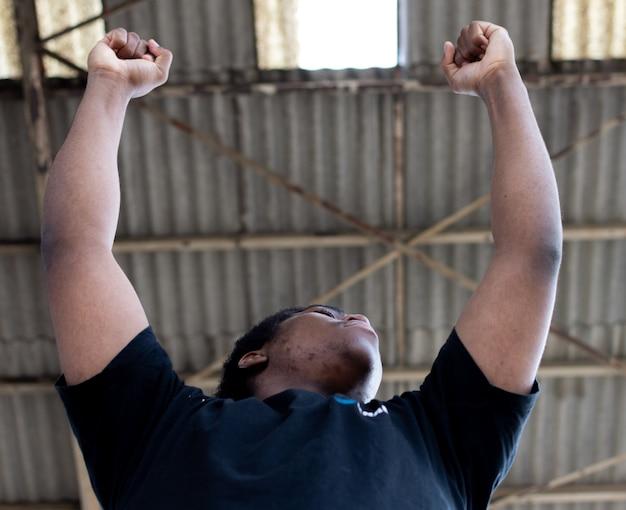 Ritratto di ragazzo nero alzando le braccia per celebrare la vittoria