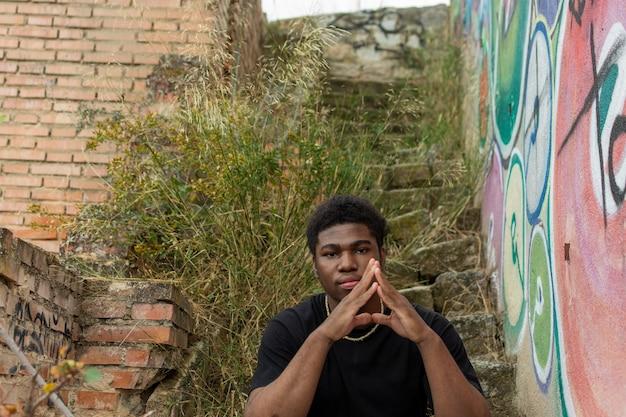Ritratto di ragazzo nero seduto in un scale abbandonate.
