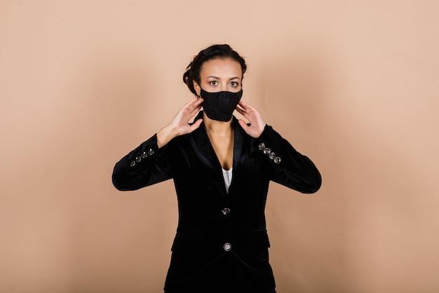 Ritratto di imprenditrice nera che indossa la maschera per il viso durante l'epidemia di virus in uno studio.