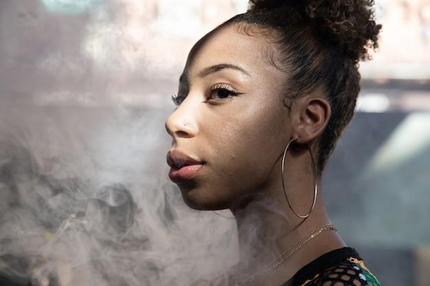 Ritratto di una ragazza nera con grandi anelli che fumano con un piroscafo e soffiano il fumo all'interno di una stanza
