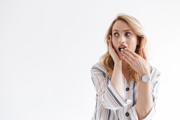Ritratto di donna europea bionda che indossa l'orologio da polso guardando da parte copyspace con la mano sulla bocca isolata sopra il muro bianco