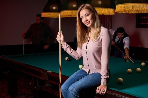 Ritratto di donna bionda seduta sul tavolo da biliardo in posa, indossando abiti casual, al bar, trascorrendo momenti piacevoli, vacanze