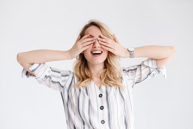 Ritratto di donna graziosa bionda che indossa l'orologio da polso sorridente e che copre gli occhi con le mani isolate sul muro bianco