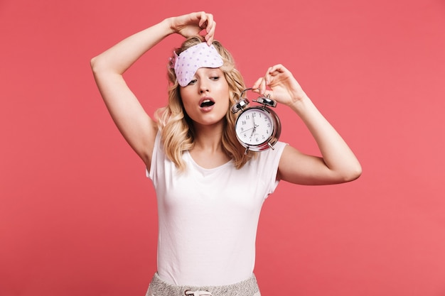 Ritratto di giovane donna bionda che indossa una maschera per dormire che tiene la sveglia dopo il risveglio isolata sul muro rosso