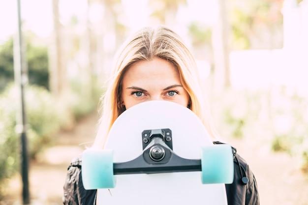 Ritratto di bella giovane donna bionda con gli occhi azzurri che tiene lo skateboard