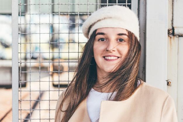 Ritratto di una ragazza bionda in un berretto e giacca beige che si appoggia su un vagone del treno d'epoca