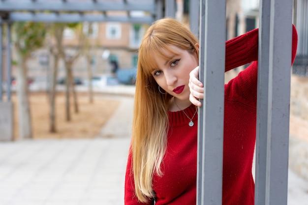 Ritratto di una ragazza bionda con rossetto rosso e maglione rosso in un quartiere residenziale