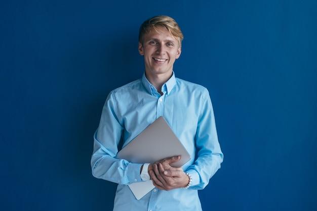 Ritratto di ragazzo biondo con laptop che indossa una camicia casual sorridente e guardando a porte chiuse.