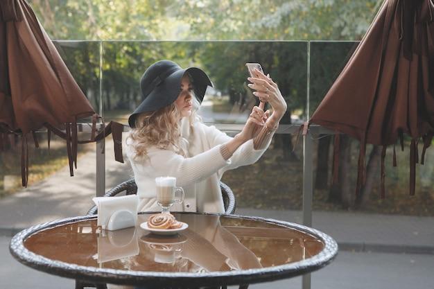 Ritratto di una signora bionda con un cappello nero a un tavolo in un caffè con uno smartphone, capelli lunghi, un cappotto beige. fare un selfie.