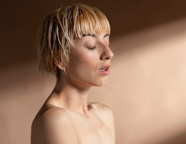 Ritratto di donna bionda dai capelli corti in posa a torso nudo
