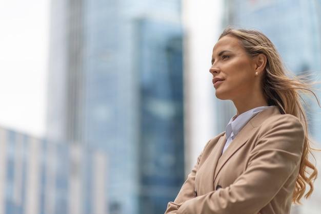 Ritratto di una donna bionda sorridente in piedi in un quartiere della città