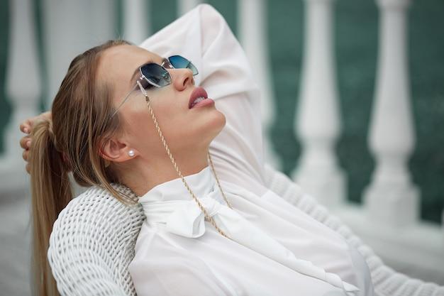 Ritratto di una bionda con gli occhiali da sole sdraiata su una sedia all'aria aperta