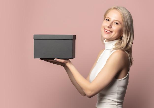 Ritratto di bionda in alto con confezione regalo nera su rosa
