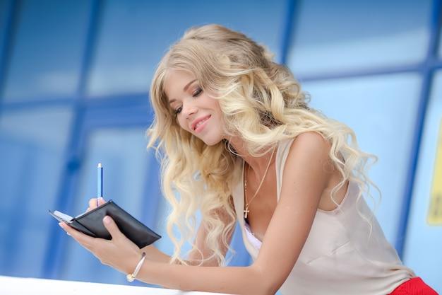 Ritratto di una donna bionda vicino con i capelli ricci e un quaderno in mano