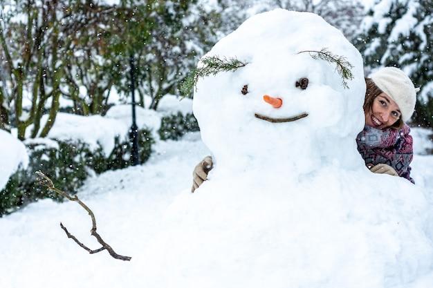 Ritratto di una donna bionda vestita con un berretto, giacca e sciarpa nascosti dietro un pupazzo di neve.