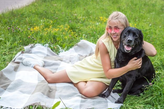 Ritratto di donna bionda in occhiali rosa e cane