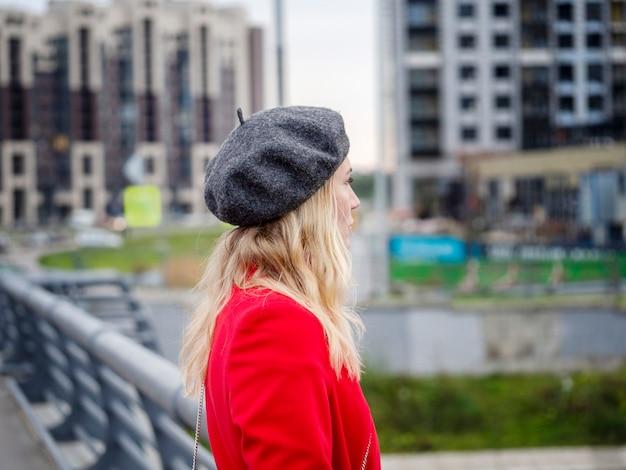 Ritratto di una donna bionda in un cappotto rosso e berretto su una città urbana sfocata.