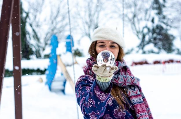 Ritratto di una donna bionda che indossa un berretto, giacca e sciarpa tenendo una sfera di cristallo in un parco innevato.