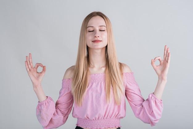 Ritratto di una donna bionda che mostra il gesto mudra