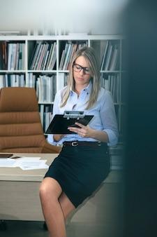 Ritratto di donna bionda che scrive appunti seduti sul suo tavolo desktop. visualizza attraverso la porta dell'ufficio.