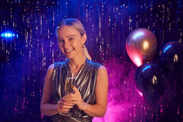 Ritratto di giovane donna bionda che tiene il bicchiere di champagne e sorride alla macchina fotografica mentre gode della festa in discoteca, copia dello spazio