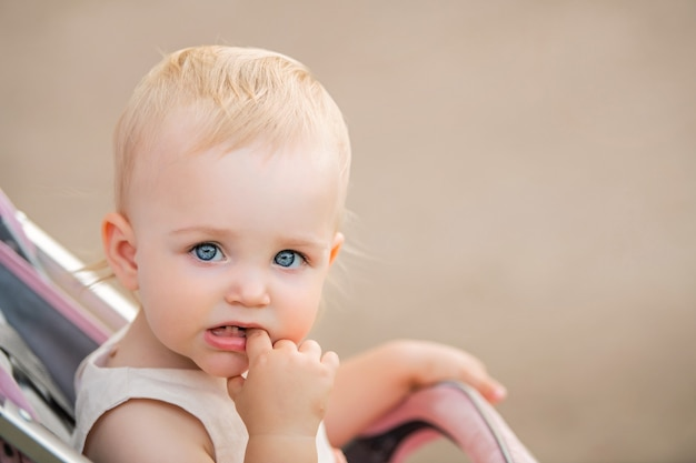 Ritratto di un bambino dagli occhi azzurri che si succhia un dito in bocca, sono visibili due primi denti.