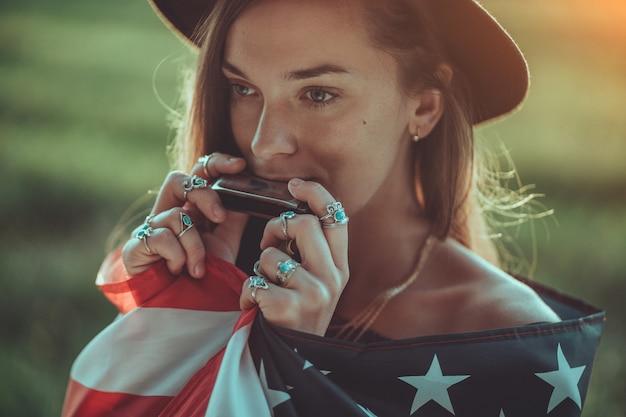 Il ritratto della donna chic di boho in cappello con la bandiera americana che indossa gli anelli d'argento con la pietra del turchese gioca sull'armonica all'aperto