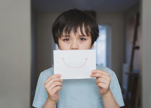 Ritratto di bambino annoiato con faccia triste che tiene carta bianca con sorriso, ragazzo bambino annoiato rimanere a casa durante l'autoisolamento