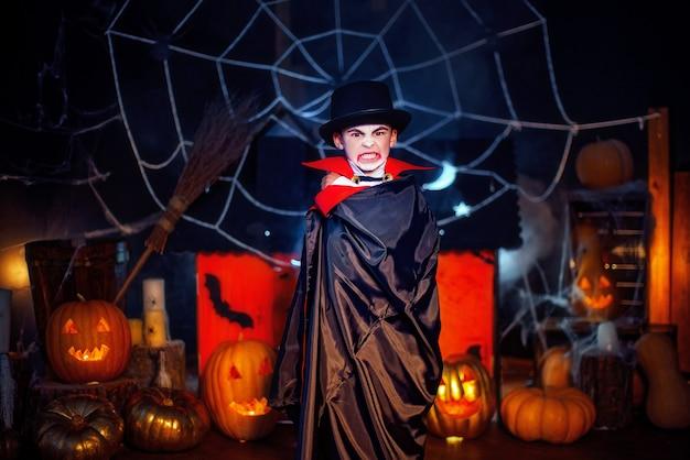 Ritratto di un ragazzo vestito con un costume di un vampiro e un cappello su sfondo grunge. festa di halloween.