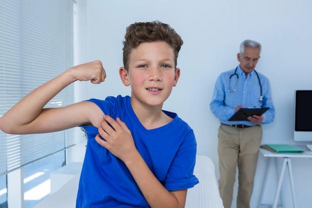 Ritratto del ragazzo che flette il suo bicipite nella clinica