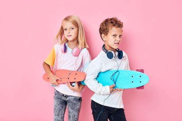 Ritratto di ragazzo e ragazza intrattenimento skateboard lifestyle sfondo rosa