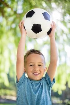 Ritratto del ragazzo che tiene un calcio in parco