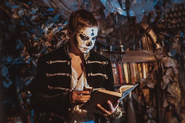 Ritratto di un ragazzo truccato da un maniaco pazzo in piedi in un interno favoloso con un vecchio libro e una candela in mano