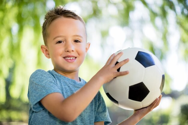 Ritratto del ragazzo che gioca con un calcio in parco