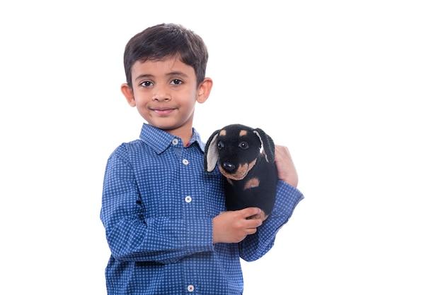 Ritratto del ragazzo che gioca con il suo animale domestico farcito sulla parete bianca