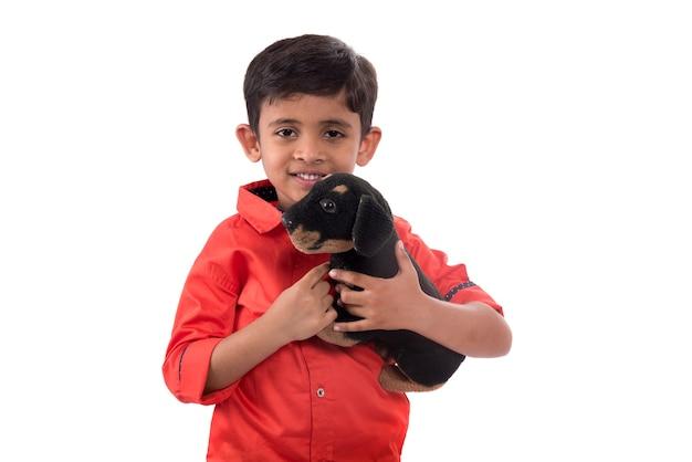 Ritratto di ragazzo che gioca con il suo animale di peluche su bianco